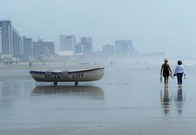 Atlantic City Lifeboat pictured with people walking on beach on a misty morning.