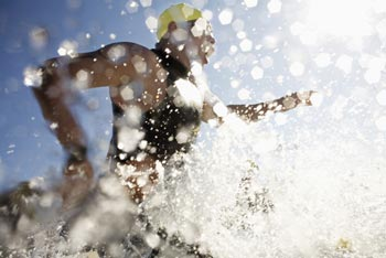 Competitive swimmer entering ocean splashes of water splashing all around them.