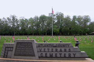 Veterans Cemetery in Estell Manor Park. Memorial visible with American Flags marking grave sites and American flag on flag pole visible.